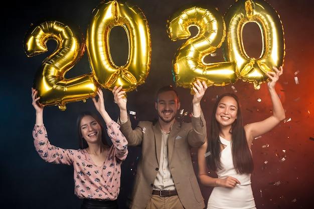 Группа друзей, подняв новогодние шары