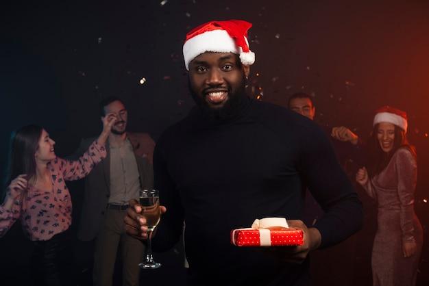 Средний снимок улыбающегося человека, пьющего шампанское на новогодней вечеринке