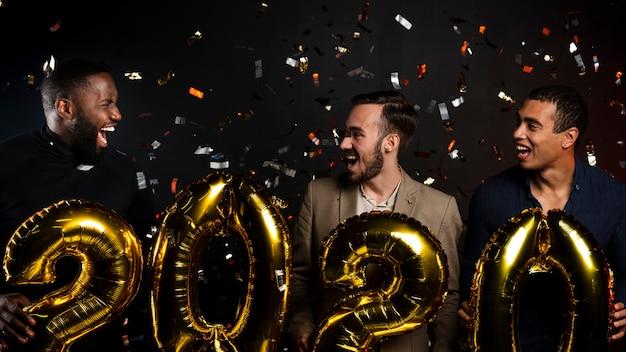 Средний снимок друзей, празднующих новый год
