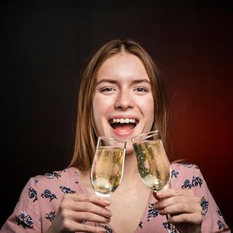 Крупным планом женщина пытается выпить шампанское из двух бокалов