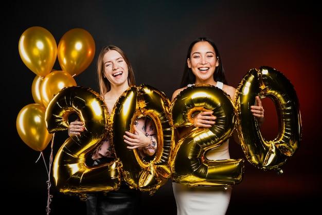 Друзья позируют с золотыми шарами на новогодней вечеринке