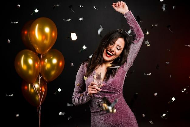 Средний снимок женщины, танцующей на новогодней вечеринке