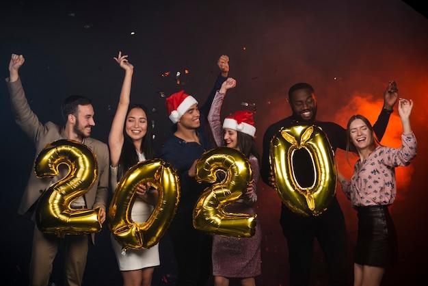 Возбужденные друзья позируют с воздушными шарами на новогодней вечеринке