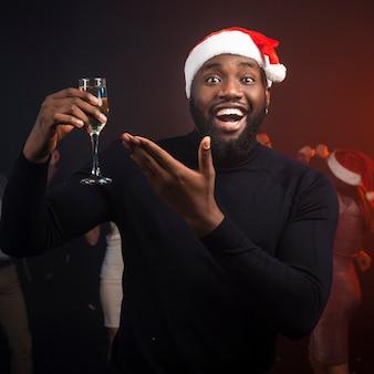 Мужчина держит бокал шампанского на новогодней вечеринке