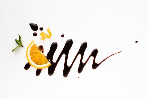 Апельсин с шоколадом на простом фоне
