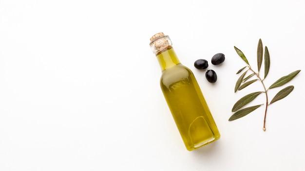 オリーブオイルボトルの葉とコピースペースとブラックオリーブ