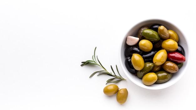 Плоский ассортимент оливки в миску с копией пространства