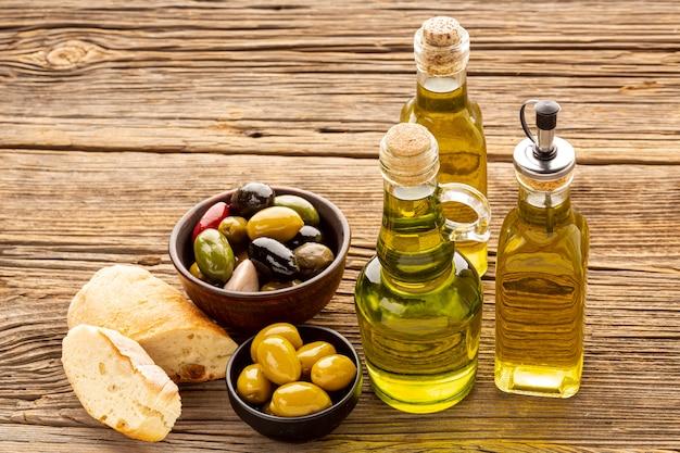Высокий угол ломтики хлеба оливковые миски и масляные бутылки