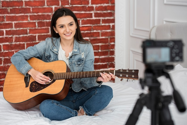 Красивая молодая женщина играет на гитаре