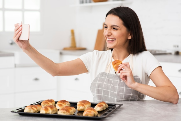 Молодая женщина, принимая селфи на кухне