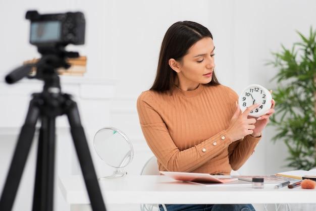 Молодая женщина держит часы на камеру