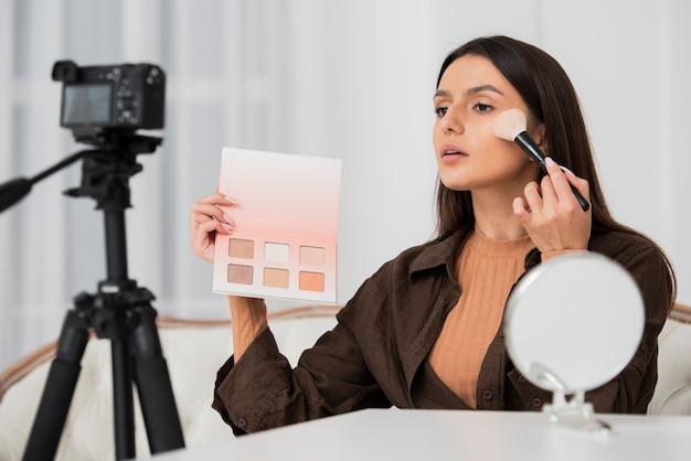 Красивая женщина делает ее макияж
