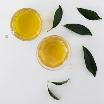 Вид сверху чаши с оливковым маслом и листьями