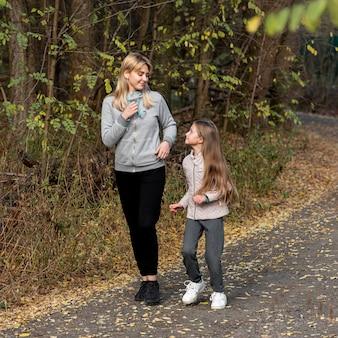 自然の中で実行しているスポーティな母と娘
