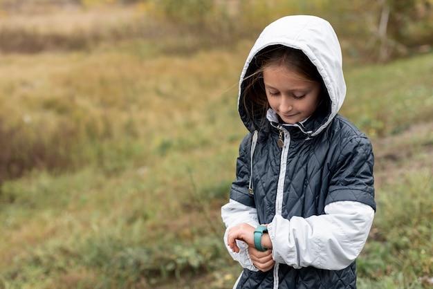 Милая маленькая девочка поправляет часы