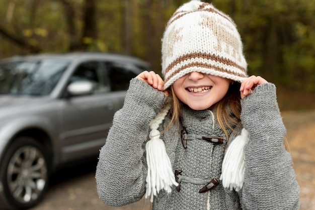 Смешная маленькая девочка закрыла лицо зимней шапкой