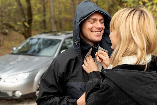 ジャケットを閉じる夫を助ける女性
