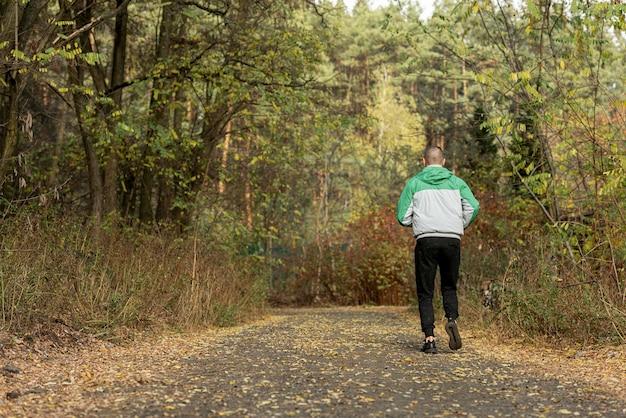 自然の中でジョギングスポーティな男の背面図