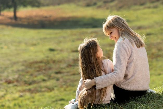 母と娘が自然の中で座っています。