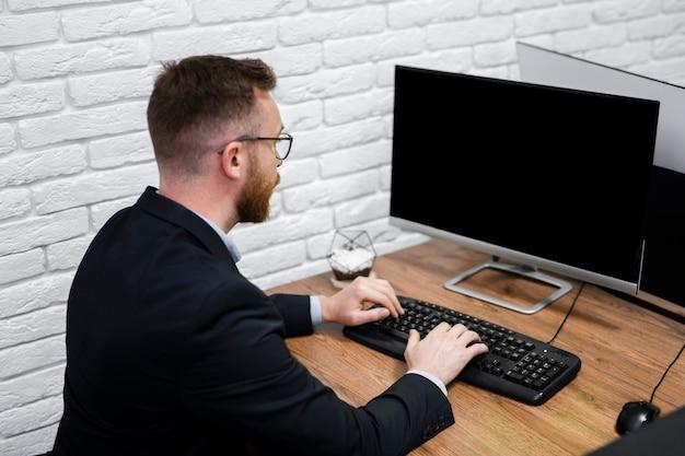 コンピューターのモックアップを見て男