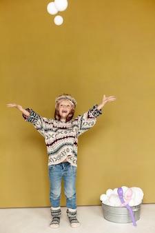 Полный выстрел ребенок играет со снежками в помещении