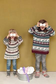 屋内で雪玉で遊ぶフルショットの子供たち