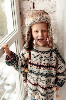 Высокий угол улыбающиеся дети с теплой одеждой позирует
