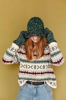 帽子で顔を覆っているミディアムショットの幸せな女の子