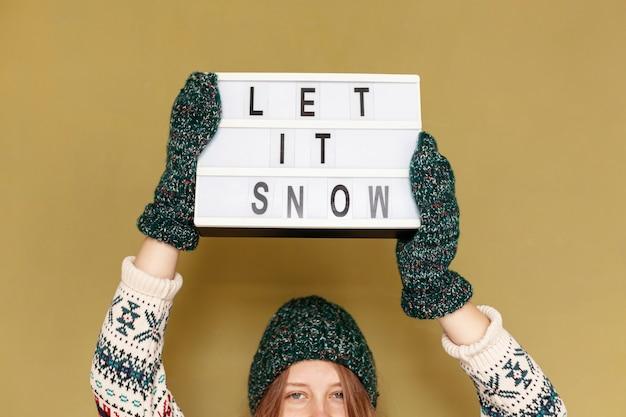 保持しているクローズアップの女の子に雪のサインを聞かせて