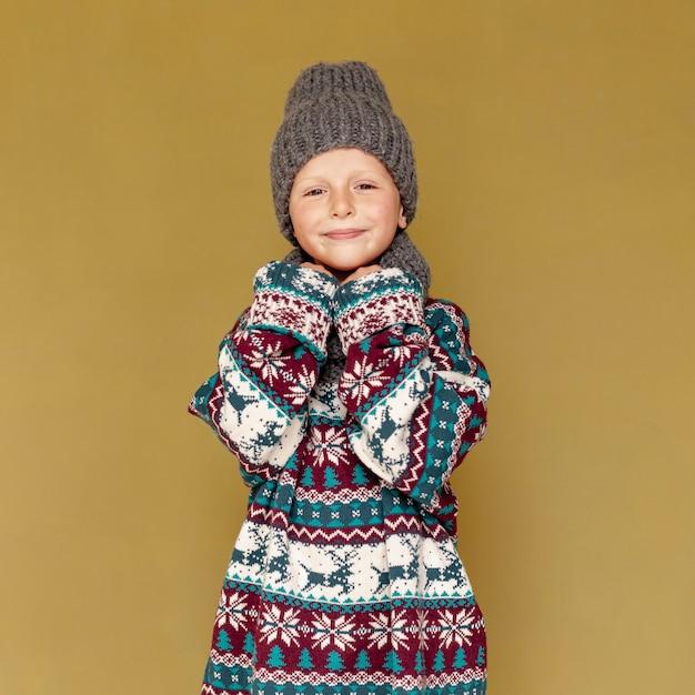 Средний снимок милый с теплой одеждой позирует