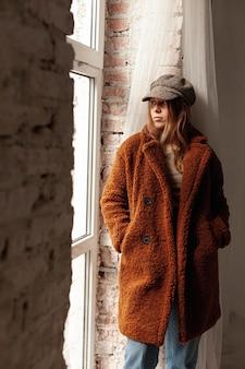 暖かいコートと帽子を持つミディアムショット少女