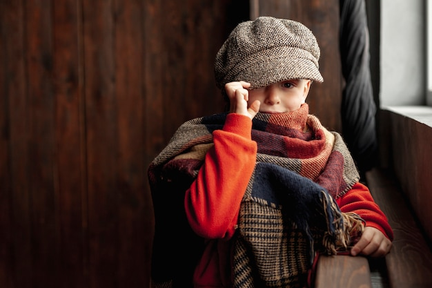 Модный мальчик среднего размера с шляпой и шарфом