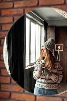Среднего выстрела модная девушка позирует в зеркале