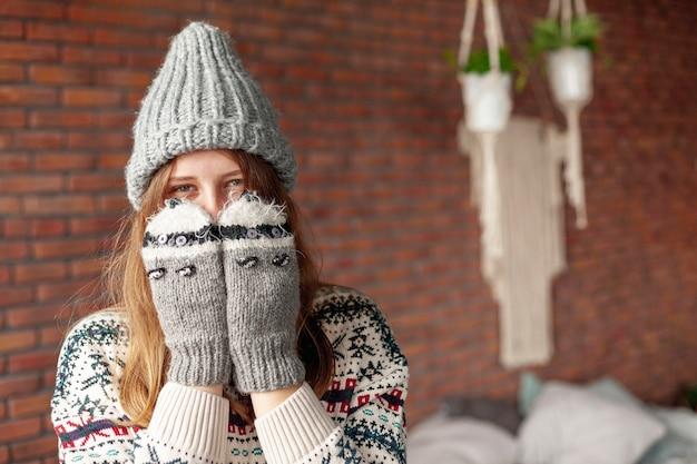 Среднего роста девушка закрыла лицо милыми перчатками