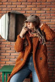 コートのポーズでミディアムショットトレンディな女の子