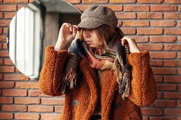 Среднего роста стильная девушка в шляпе позирует