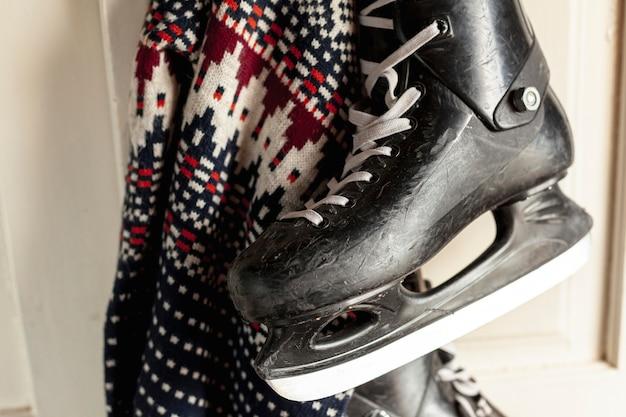 Крупный план с ледяными коньками и свитером на двери