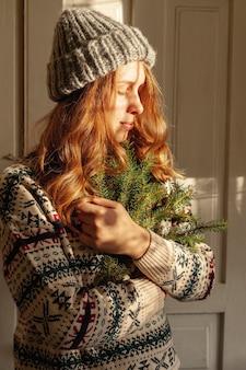 Средний снимок девушка в шляпе, держась за ветки ели