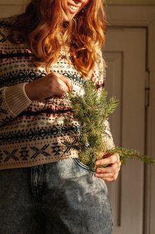 モミの木のクローズアップの女の子が屋内で小枝します。