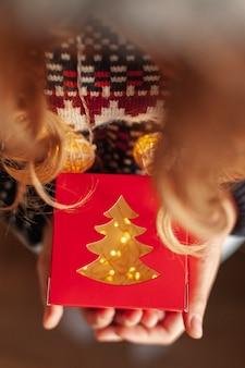 ギフトとクリスマスライトのクローズアップの女の子