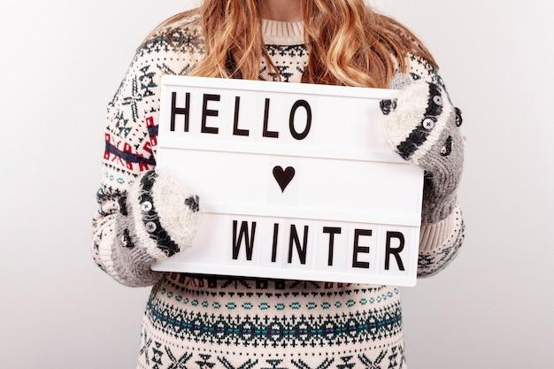 Девушка конца-вверх держа здравствуйте! знак зимы