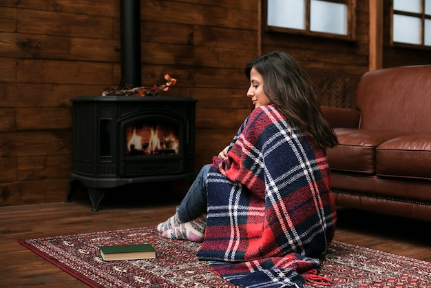 暖炉の横にある豪華な若い女性