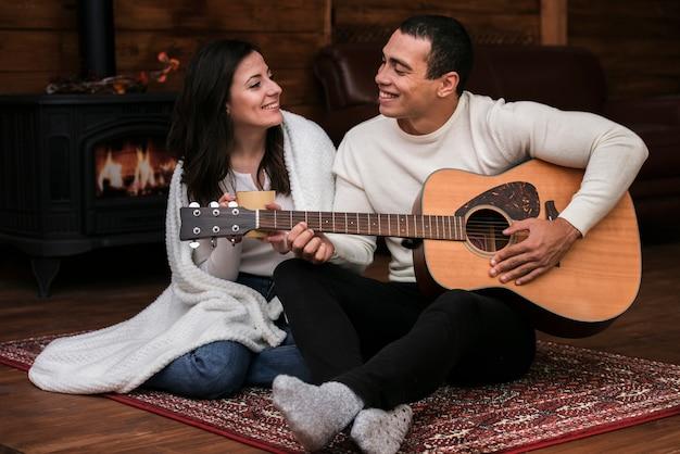 若い男が女性にギターを弾く