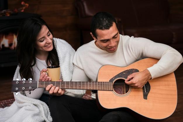 彼のガールフレンドのためのギターを弾く男