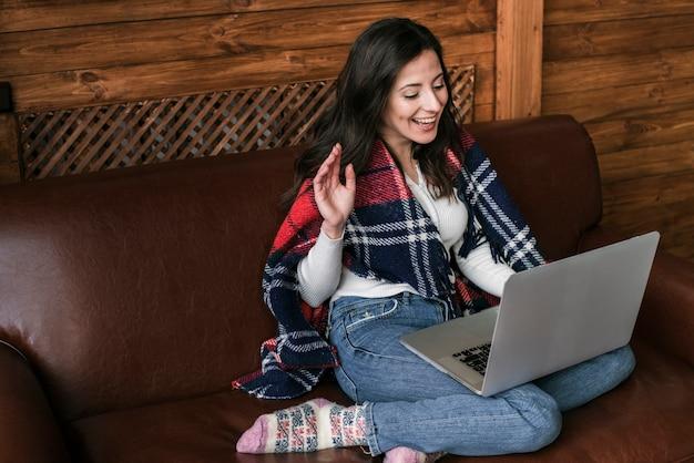 ラップトップを笑顔で若い女性