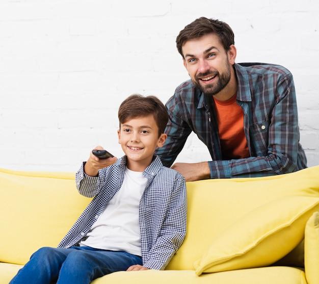 リモコンを押しながら父親と一緒にテレビを見ている息子