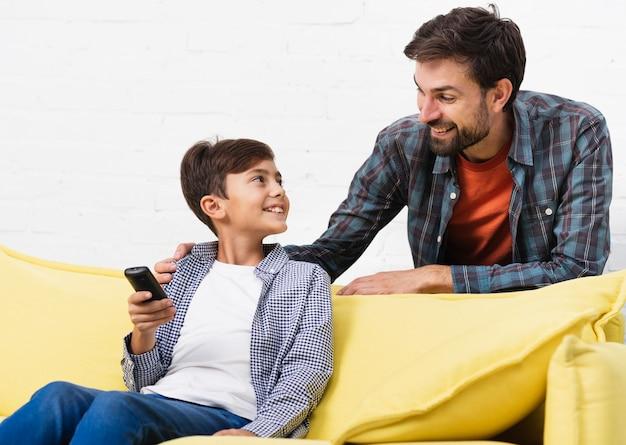 Сын держит пульт дистанционного управления и смотрит на своего отца