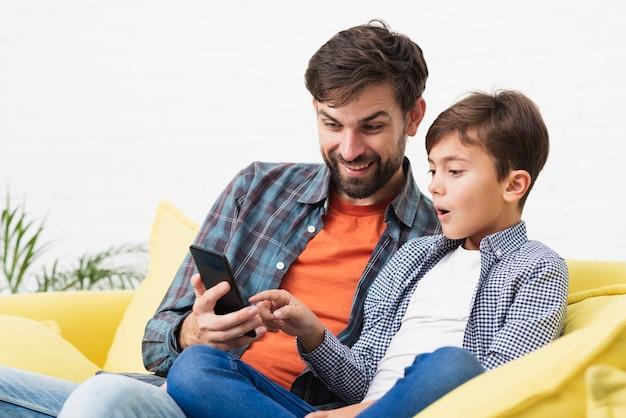 Удивленный сын и отец, глядя на телефон