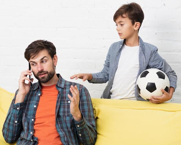 ボールと電話で話している父を保持している息子