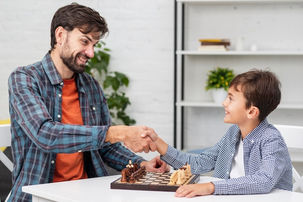 Отец и сын пожимают друг другу руки перед шахматами